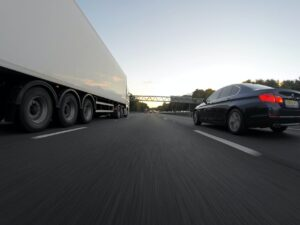 blue infiniti sedan running on road togerther with white freight truck